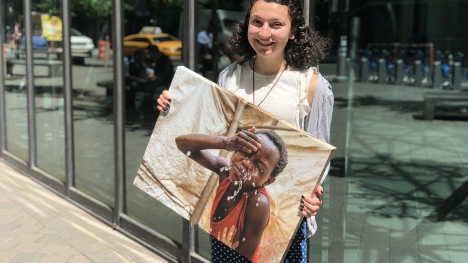 CMMB intern Grace holds a canvas image of a child CMMB serves in the field