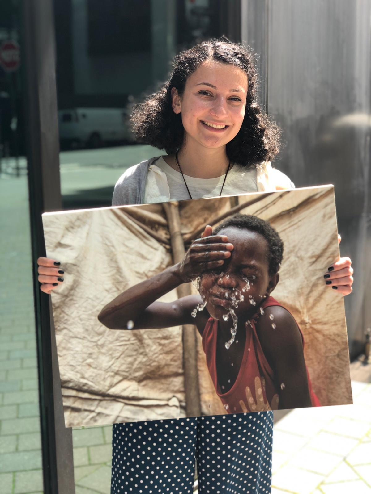 Grace is a CMMB intern. She poses outside with a canvas image of a child we serve in the field