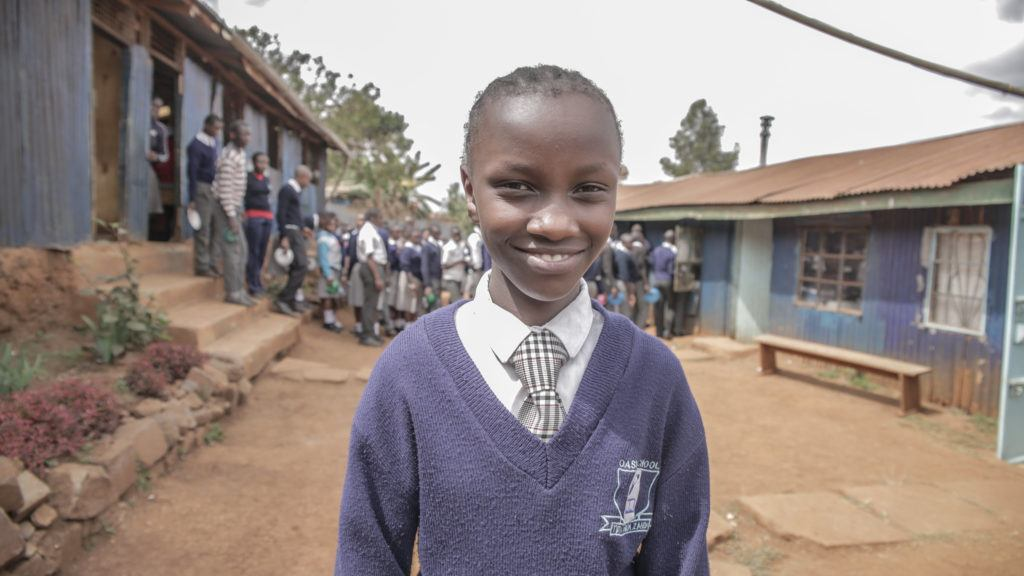 Leah, a DREAMS Student, Stands outside of her school