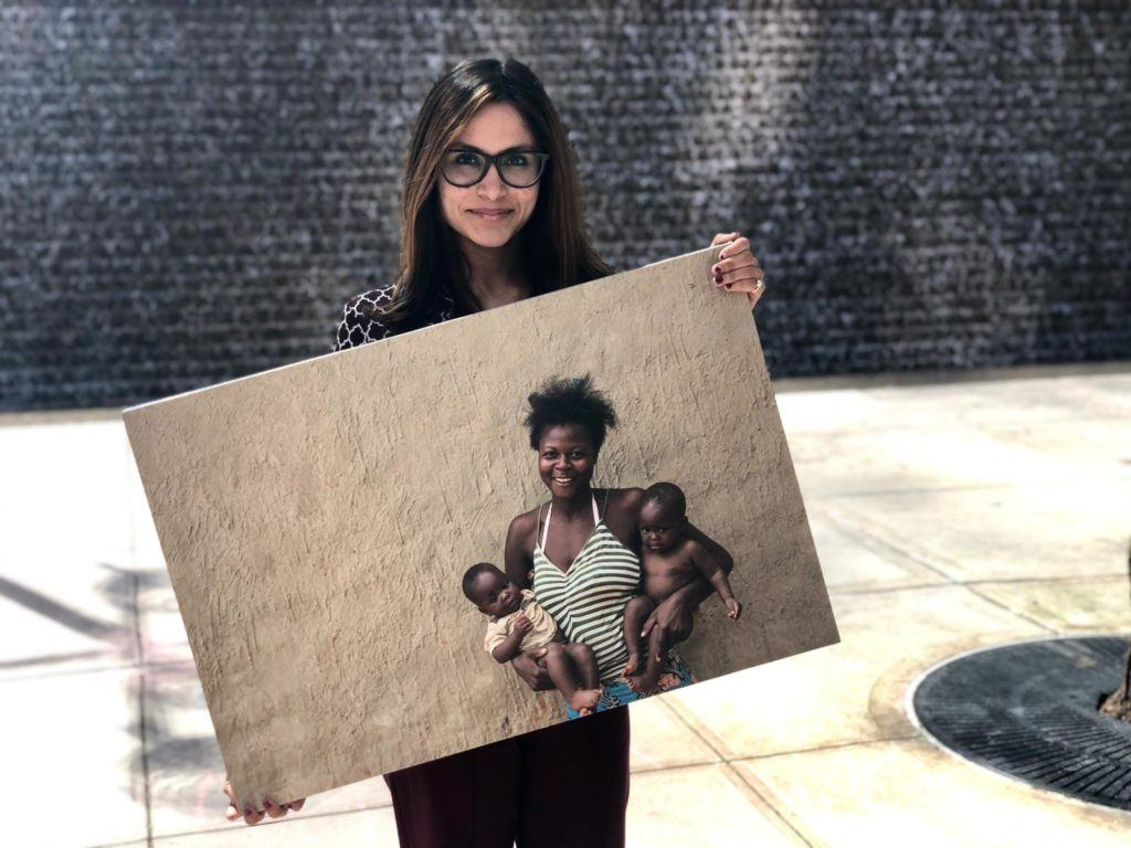 Marisha our summer intern poses outside with a canvas photo of a mother served in the field