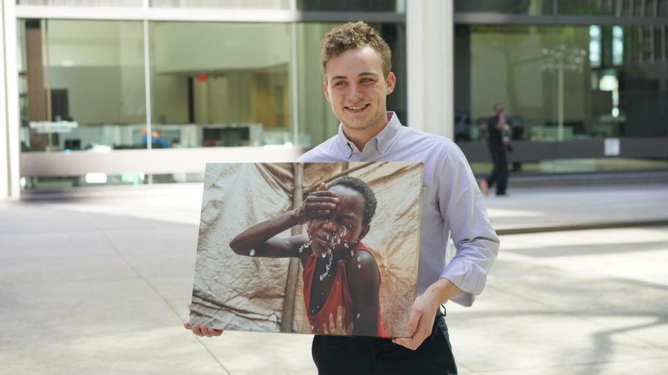 Nicholas is a CMMB intern who poses outside with a canvas image of an individual we serve