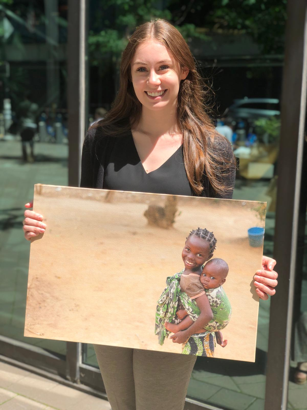Nina is a CMMB intern and she poses outside with a canvas image of two children we serve in the field