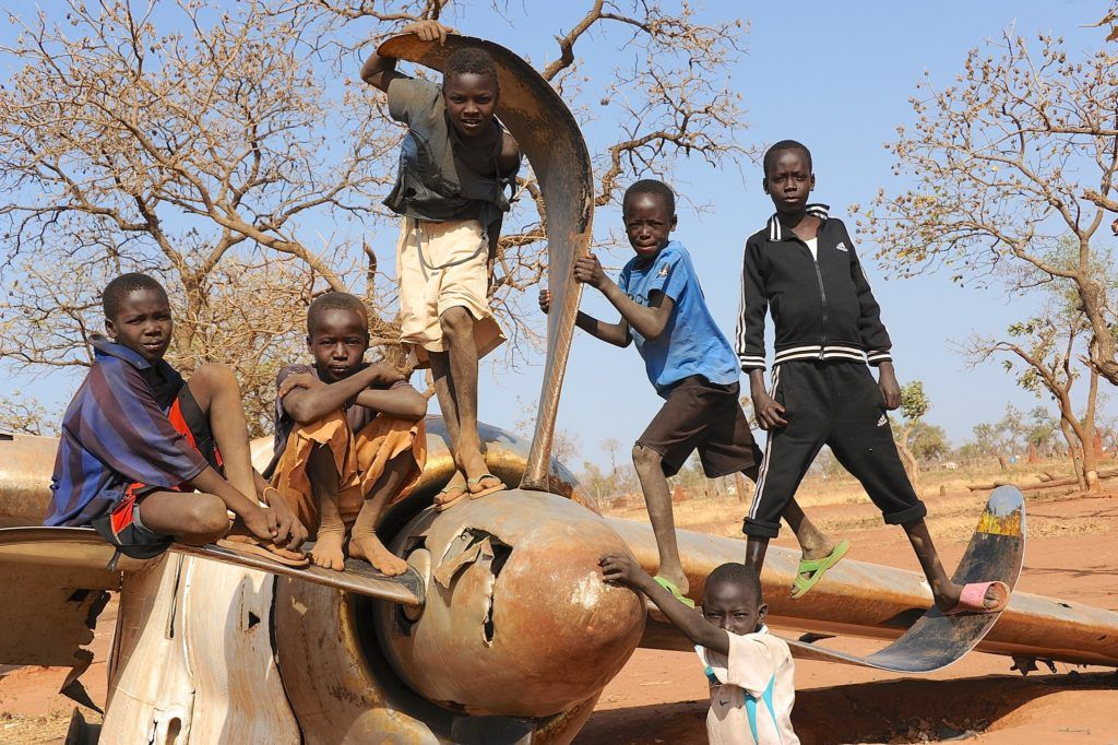 Nuba children standing on a crashed plane