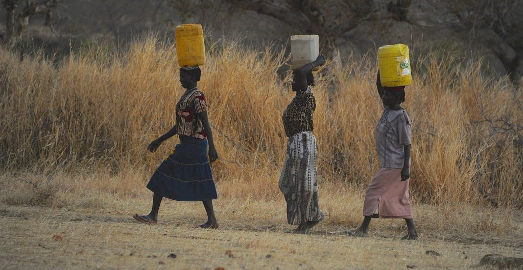 Nuba women carrying water on their heads