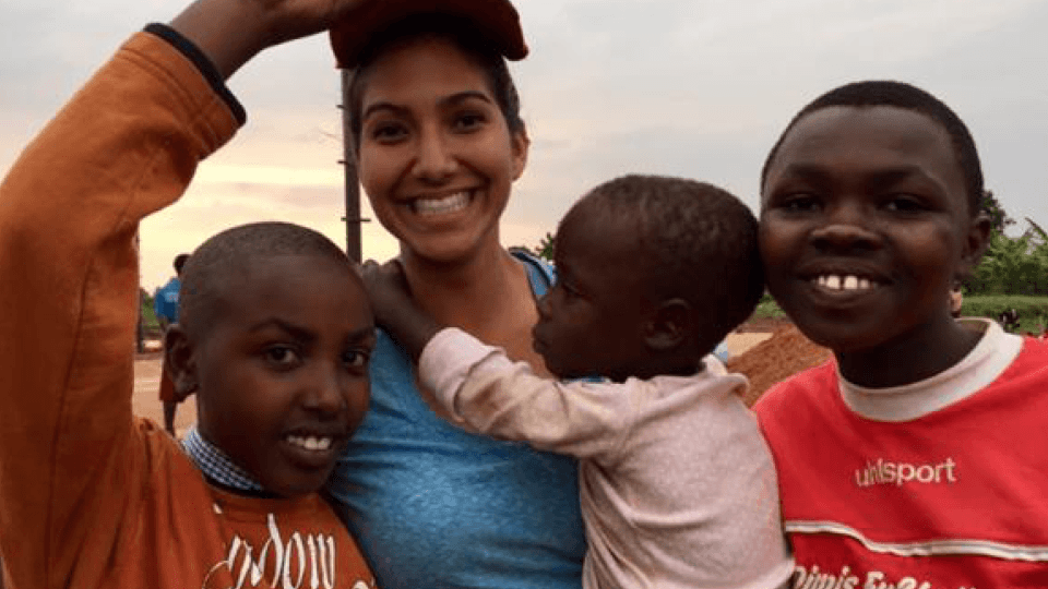 Samantha in Rwanda with children she served
