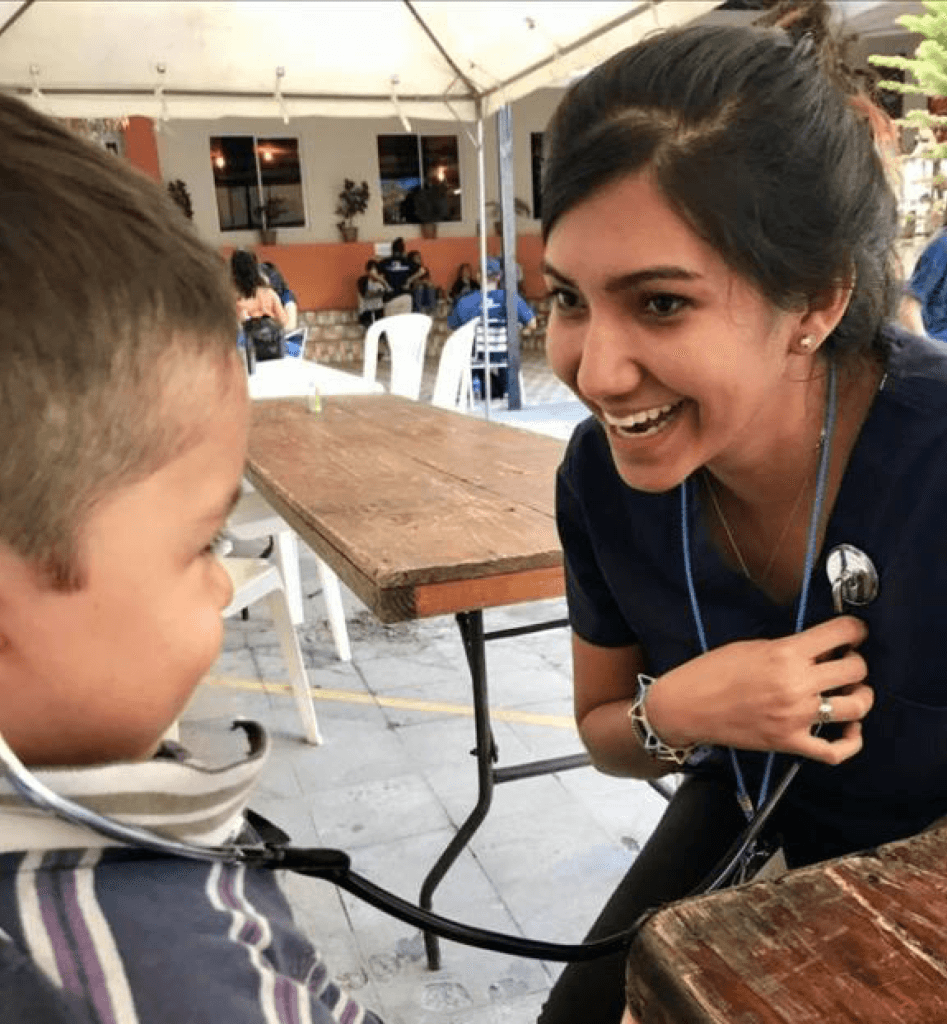 Samantha letting a little boy in El Salvador listen to her heartbeat