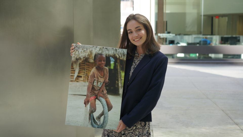 Sophia is a CMMB Intern, in this photo she poses outside with an image of a child we serve in the field