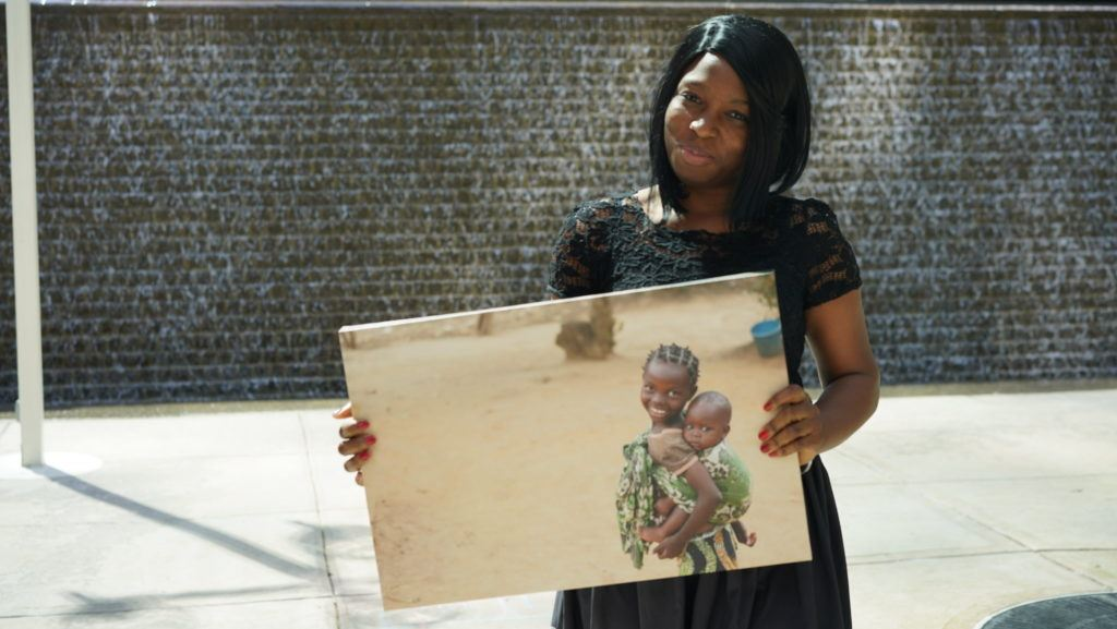 Tope, A CMMB intern poses with a canvas image of a child we serve