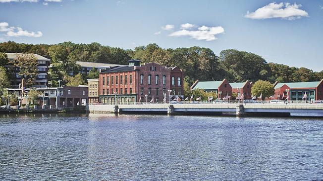Landscape image of Westport Connecticut. The image features water the river and brick buildings