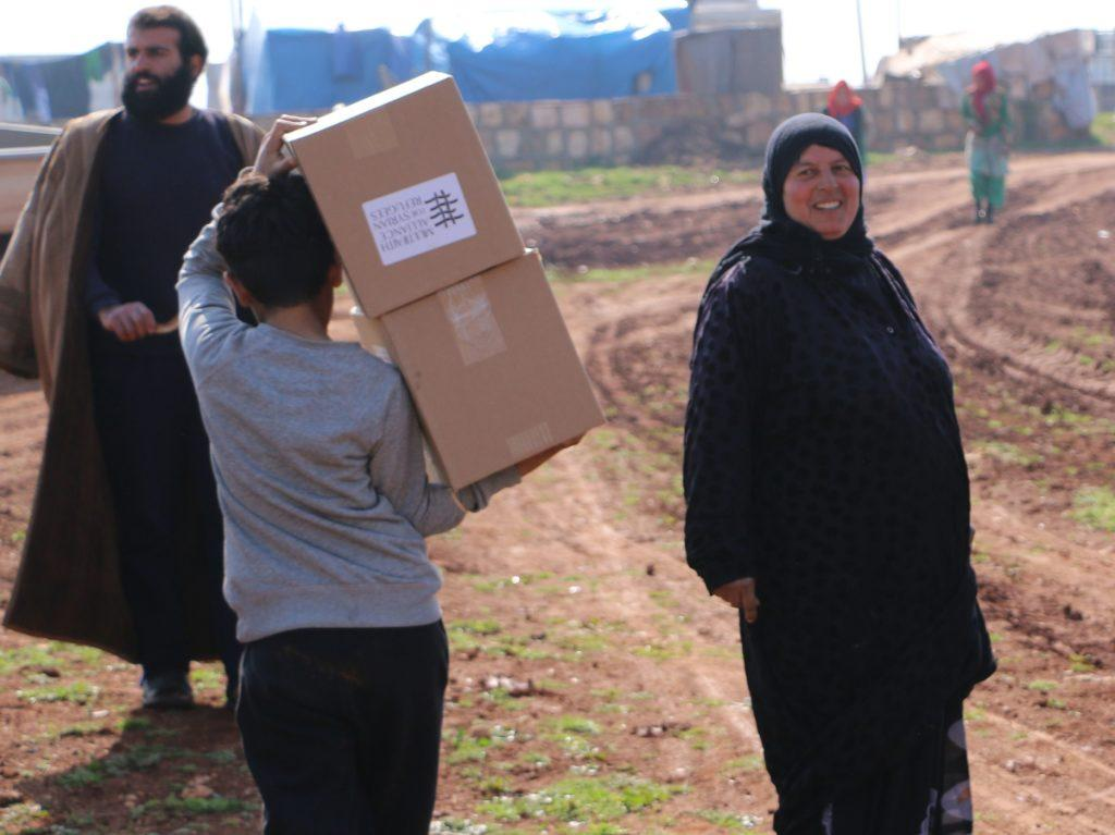 syrian woman and child carrying MFA supplies