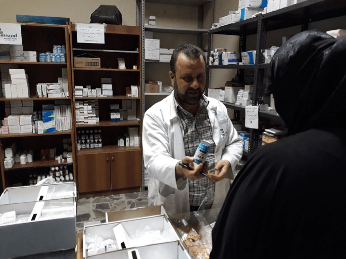 woman receiving drugs from free pharmacy