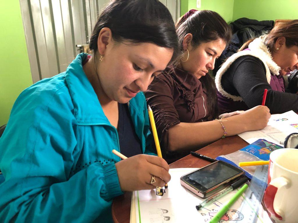 A mother in Peru sits in English Class. She participates by completing a worksheet independently