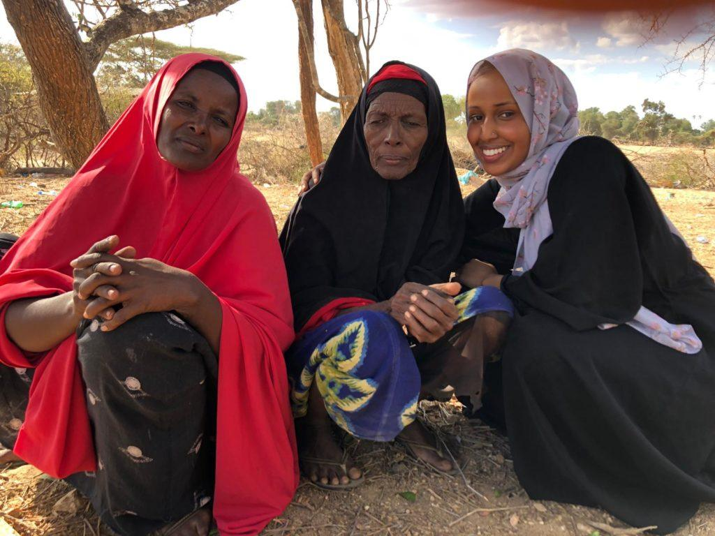 Three women wearing head scarfs. Asha, far right, is a St. Kate's student who is completing her practicum with our team in Kenya.