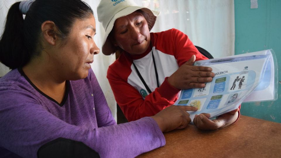 A cmmb staff member teaches a community member about gender based violence