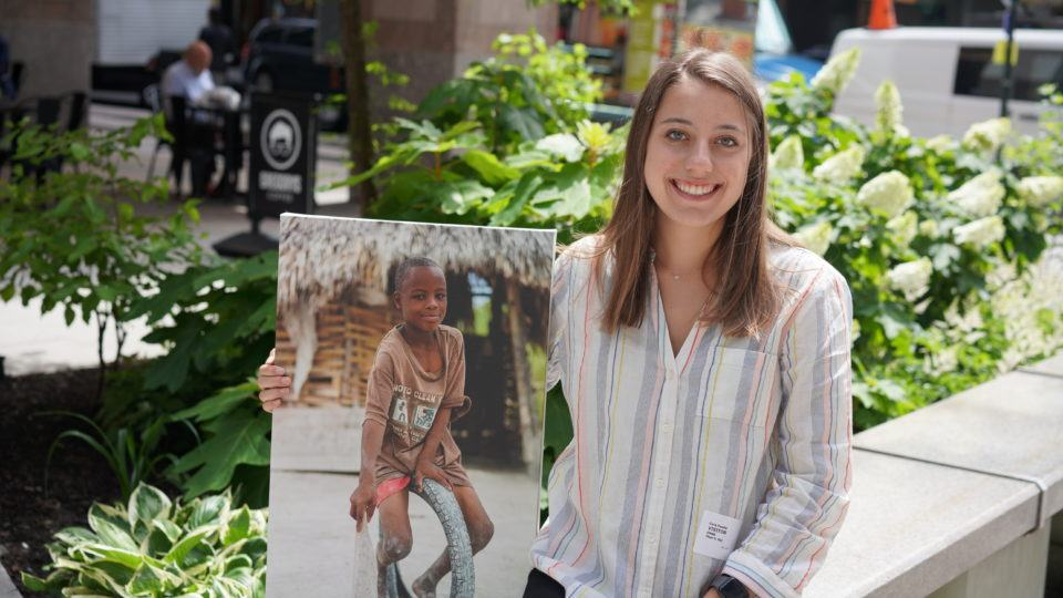 Carly Fassler outside holding a canvas photo of a child served in the field by CMMB