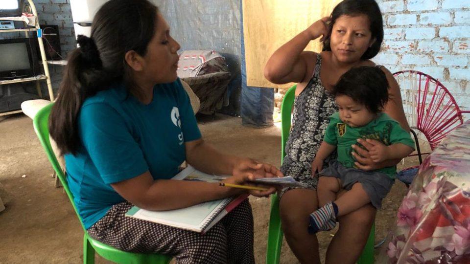 Diana sits with a community member in Peru
