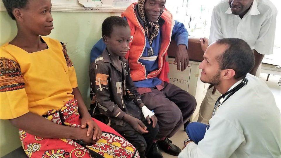 Dr. Jose kneeling in front of patients