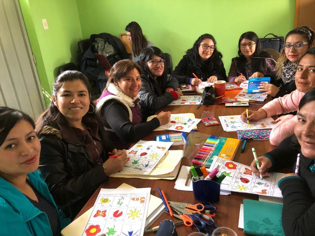 Peruvian women sitting around a table for English class