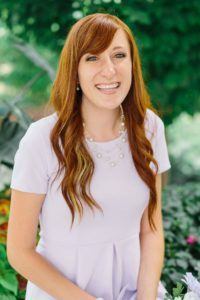 A woman with a big smile and red hair. She is one of our volunteers who will serve as a nurse assistant in Peru.