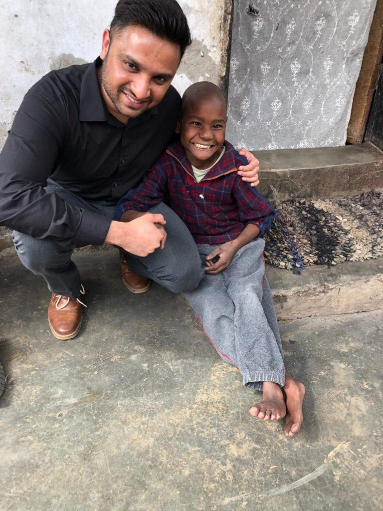 Raskeh, St. Kate student, meets with beneficiaries in Zambia. Here he is with a young Zambian boy who suffers from a physical and intellectual disability. This is the population that Rakesh is working with through the GHR/CMMB Kusamala+ program.