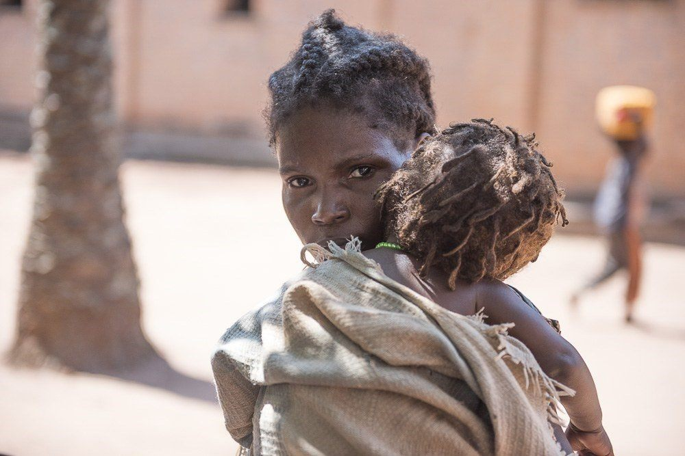 South Sudanese mom holds her baby to comfort her