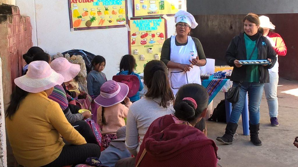 Workshop on healthy food recipes - a woman wearing a chef hat presents to the group