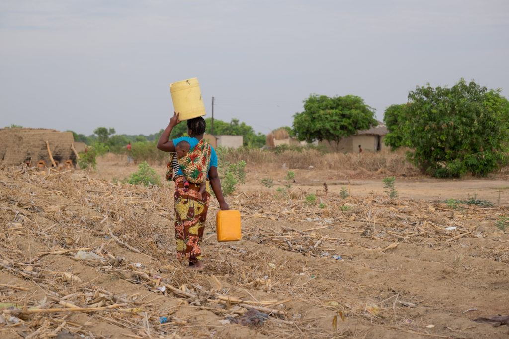 A woman carries water over head and by her side. She carries a baby with her as well