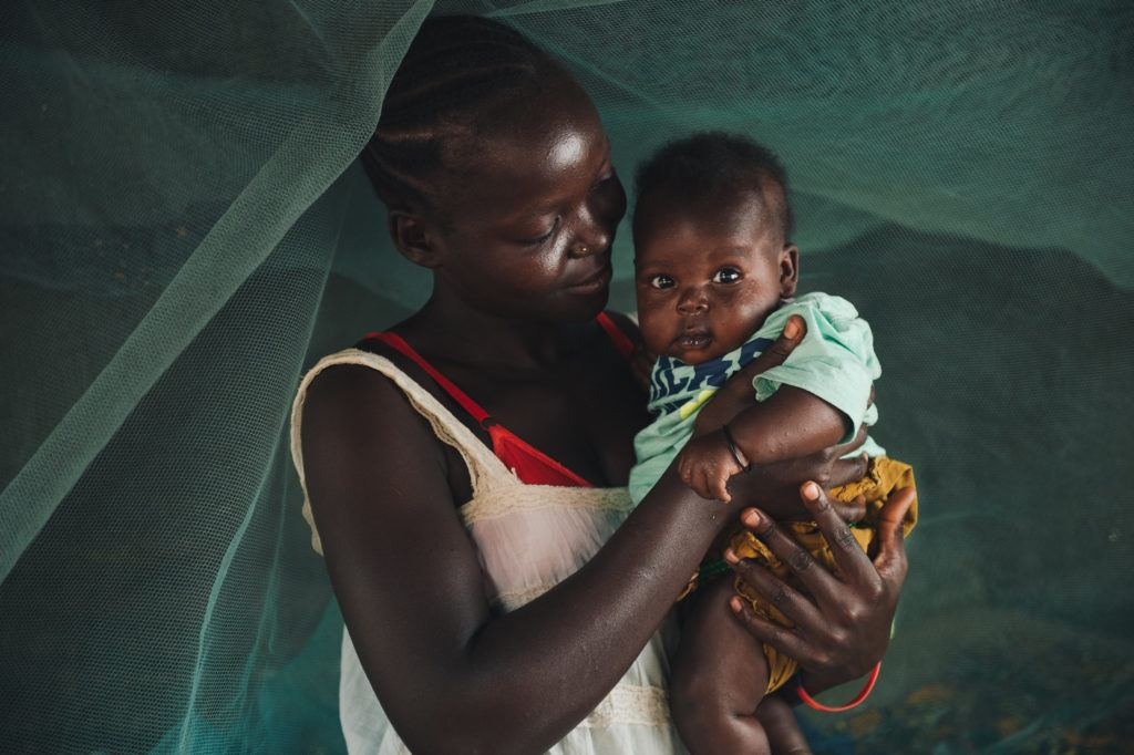 A young mother holds her child. They stand under a mosquito net. She is among the rural women that we celebrate on international day of rural women.