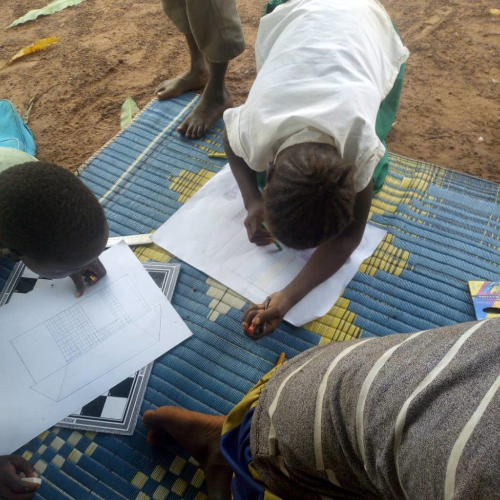 Children in South Sudan sit together and draw what peace means to them