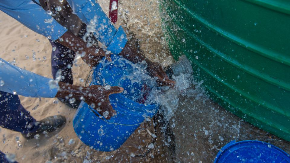 Children collect water from. It is spraying around the bucket
