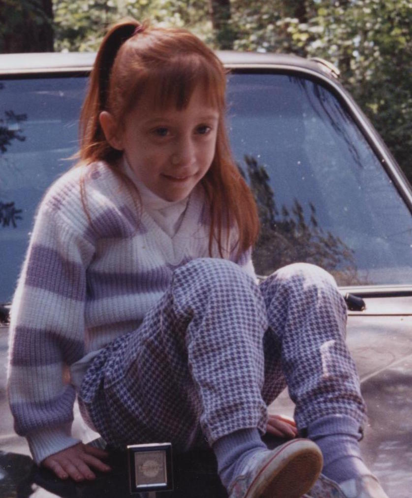 Mandi as a child sitting on the hood of a car