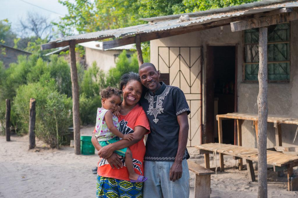 Pamela stands with her husband and baby - she is part of the village saving loans program at CMMB