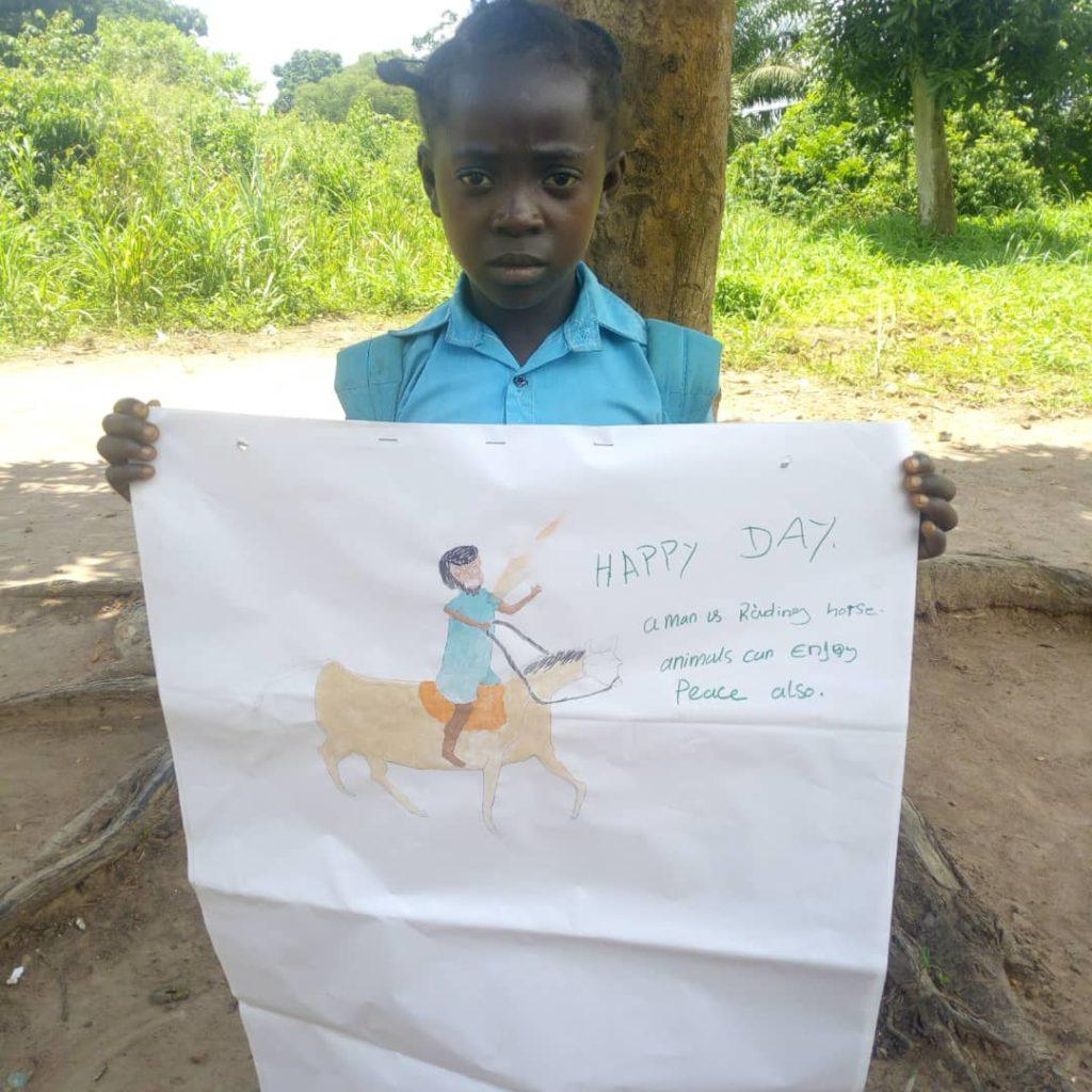 A child in South Sudan holds up a drawing of what peace means. Animals can feel peace too