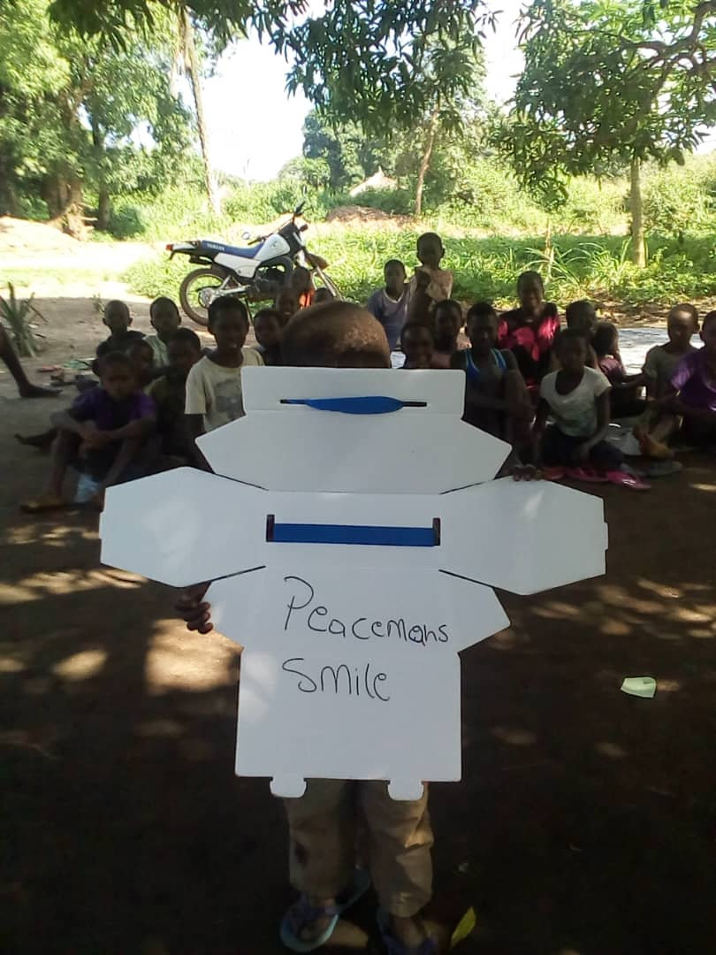 Peace means a smile. A child in South Sudan holds a poster that shares these words.