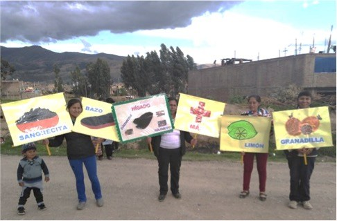 Peruvian women hold up signs of different foods that promote a healthy life.