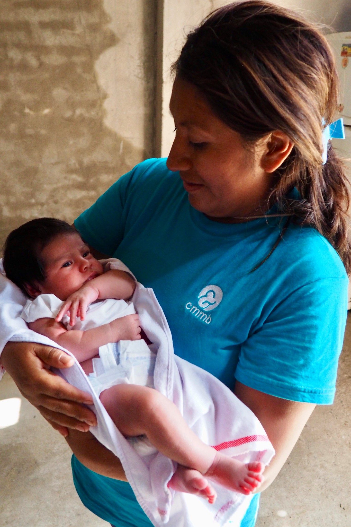 Silvia holds a newborn in her community. She is a CHW and part of her role is to identify children at risk for anemia
