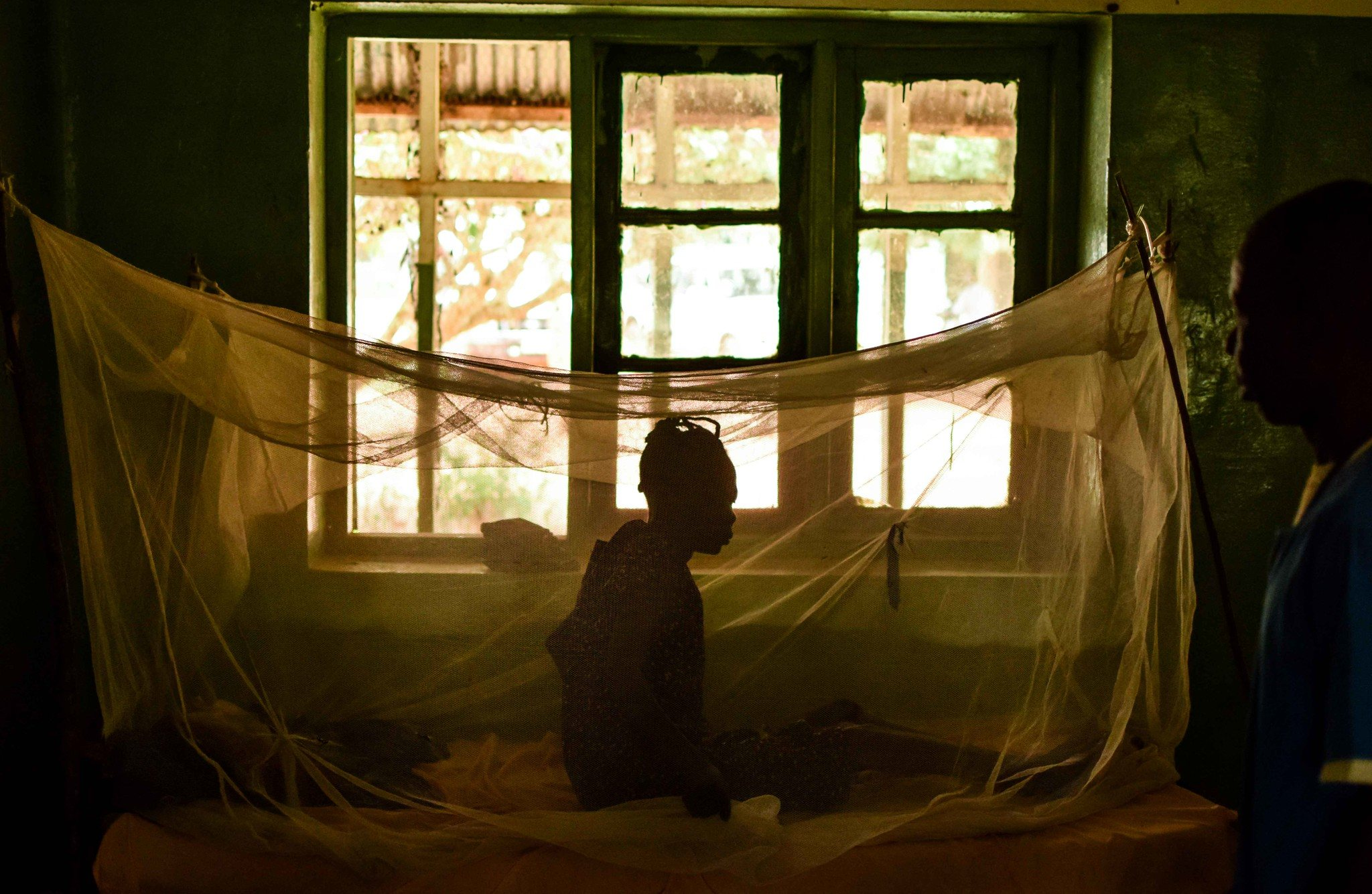 Woman sitting under a malaria prevention net in a dark hall of the St. Therese Hospital in South Sudan