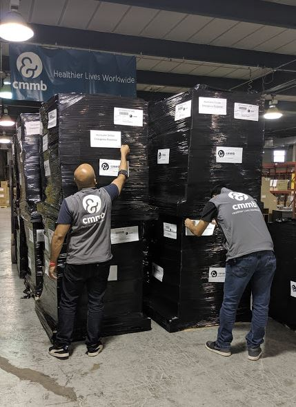 Two men wearing CMMB branded vests prepare boxes of relief for shipment to the Bahamas after Hurricane Dorian.