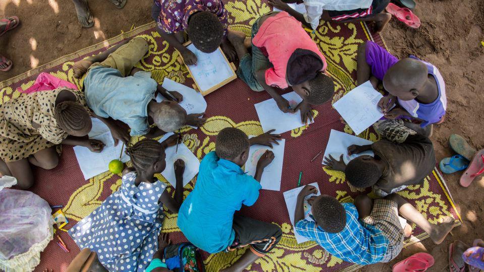 children drawing together on a blanket