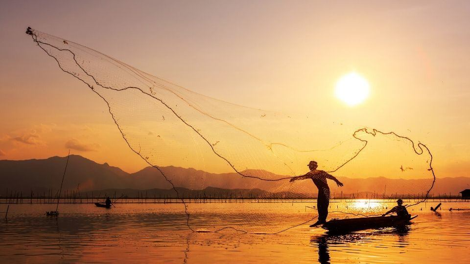 fishermen throwing a net in the water at sunset