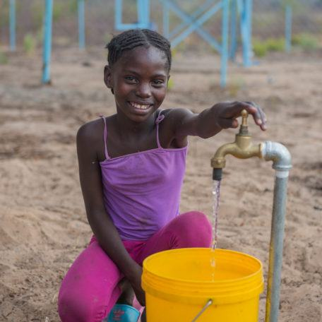 girl collecting water in zambia