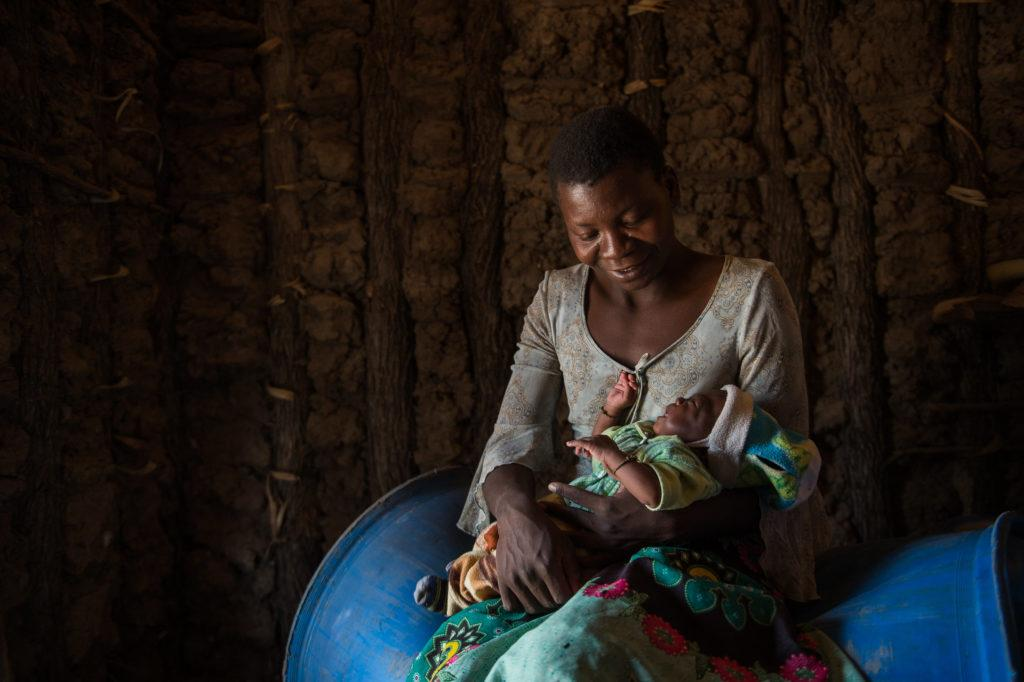A mother holds her child in her home. At CMMB we are celebrating Mother's Day