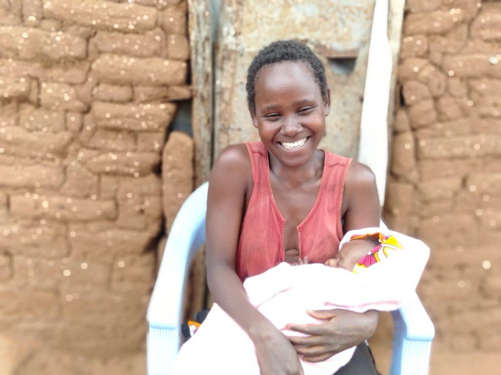 A mother smiles holding her baby
