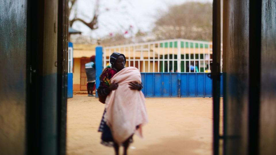 A mother walks towards to entrance of the hospital