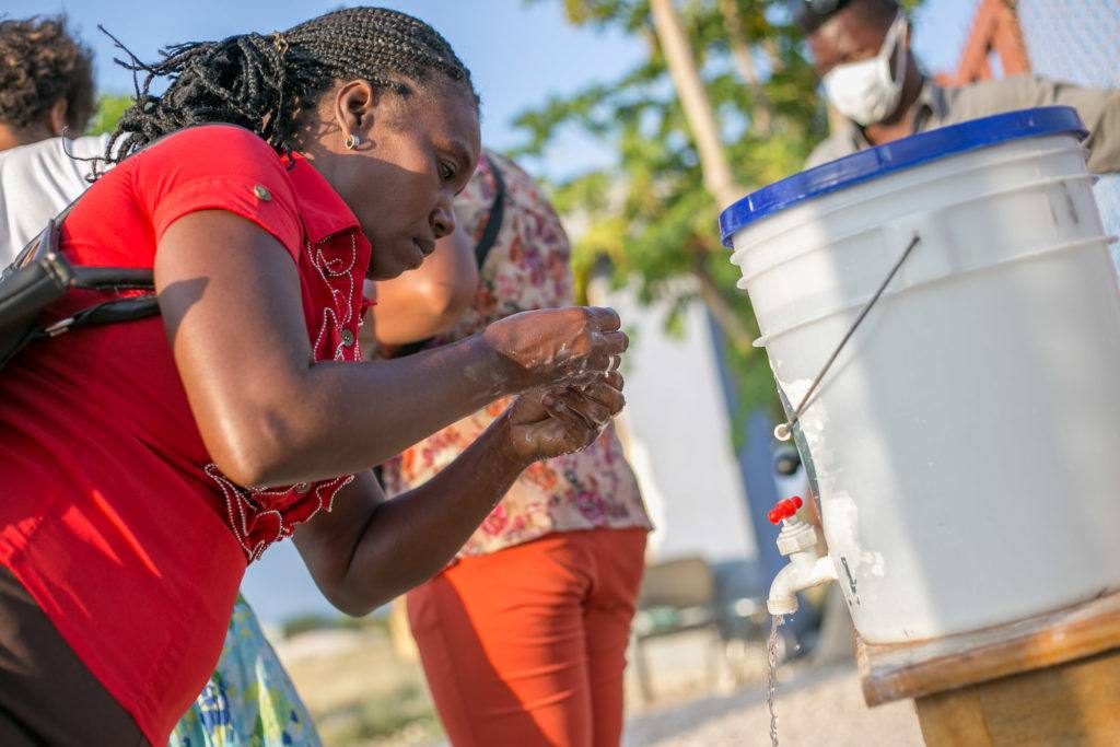 A woman washes her hands at designated hand washing stations