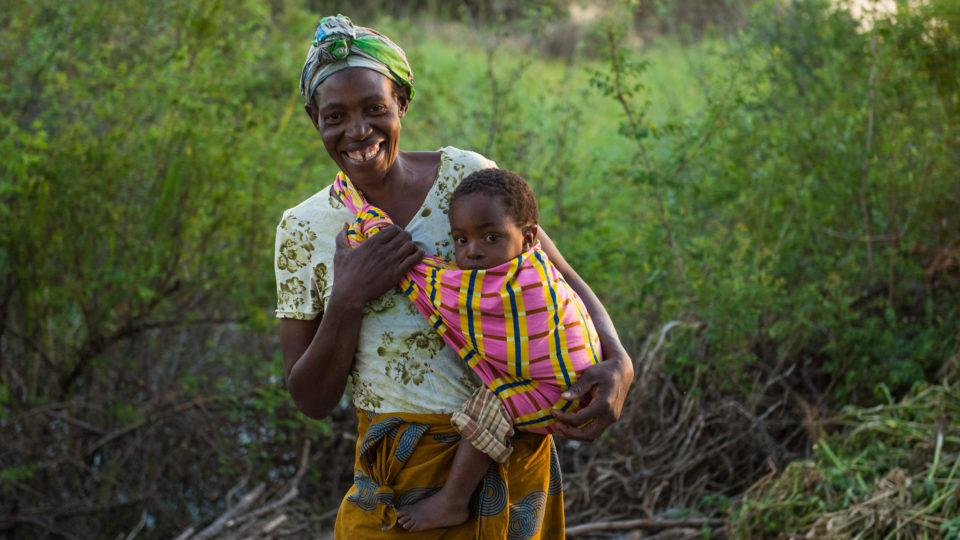A mother in Zambia holds her baby while standing in her garden. At CMMB we are celebrating Mother's Day