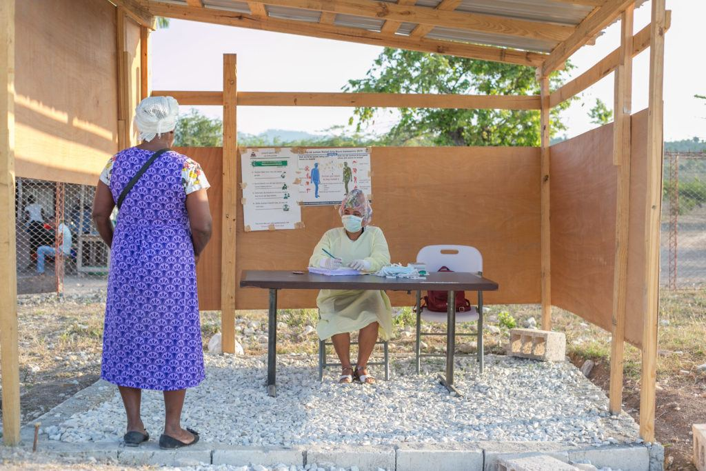 A patient waits outside at screening center in Haiti