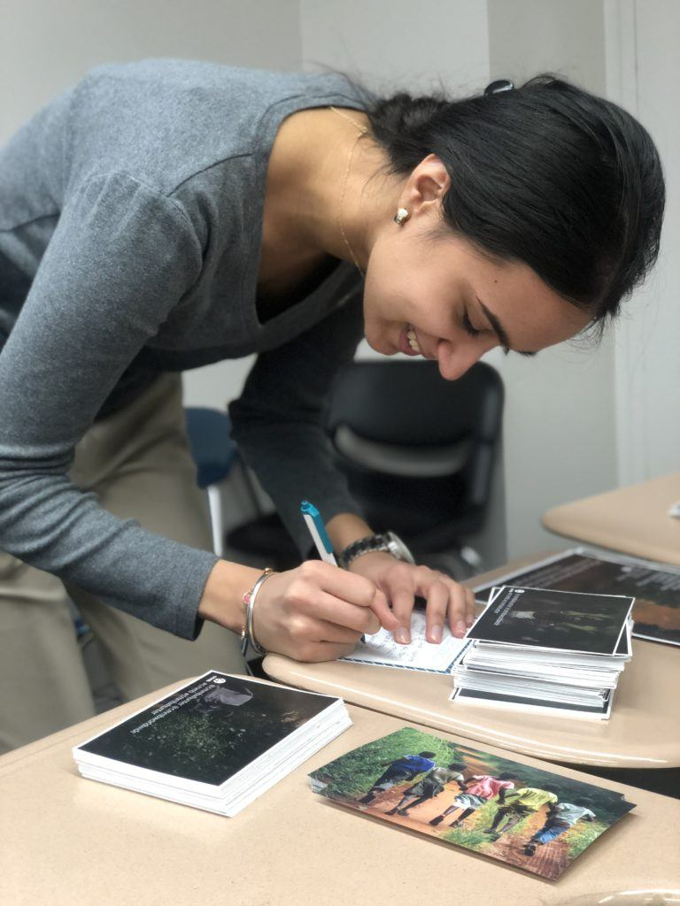 priya signing a card for a child soldier