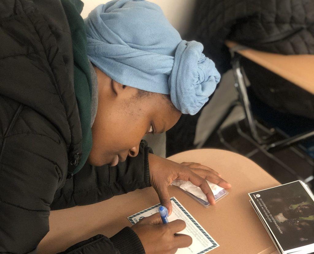 student signing postcard