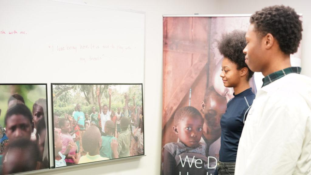 students looking images from child soldier exhibition